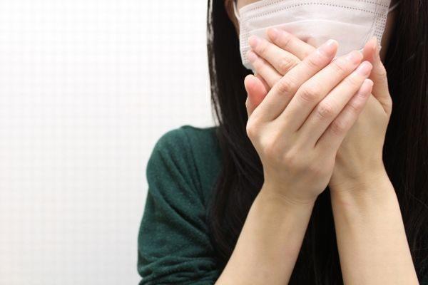 うつらないように咳を抑える女性