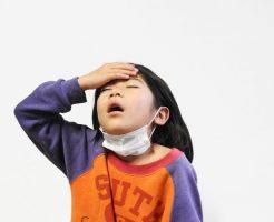 頭痛で頭を押さえる子供
