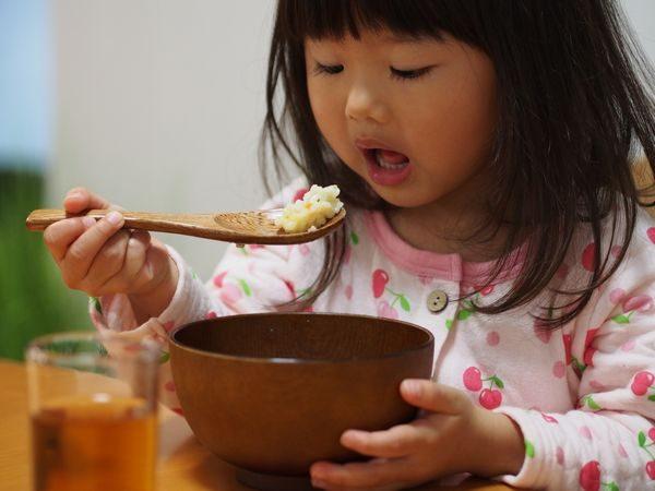 おかゆを食べる子供
