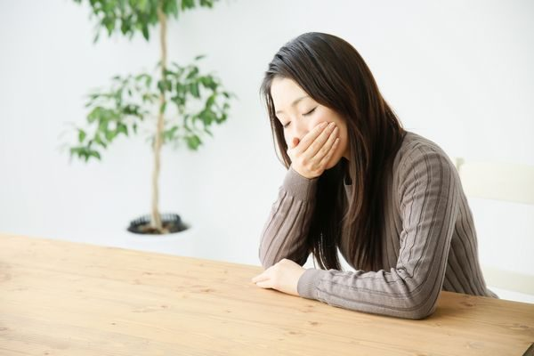 吐き気で口を抑える大人の女性