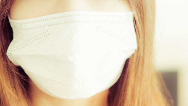長引く夏風邪でマスクを着ける女性
