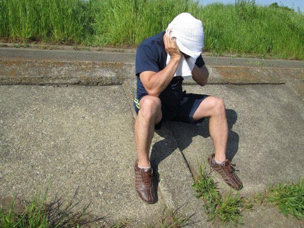 熱中症の症状で座り込んだ大人