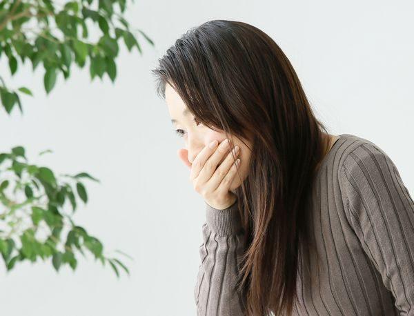 口内炎の口の痛みに口を押さえる妊婦