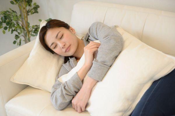 お腹の痛みで横になる女性