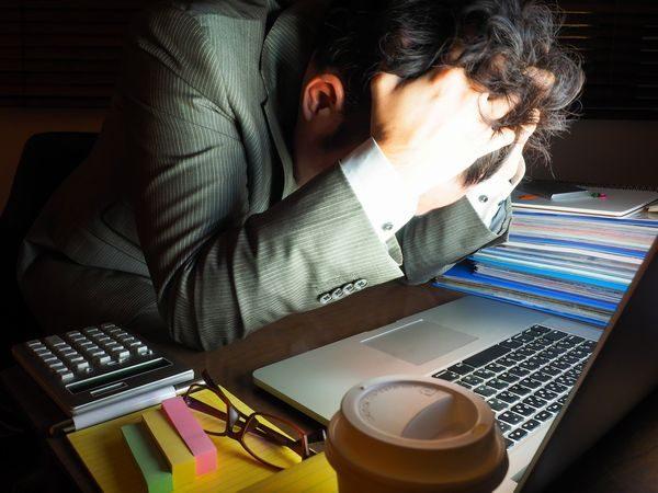 ストレスと疲れで突っ伏す大人