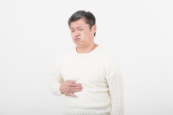ご飯を食べた後に胃の痛みで苦しむ男性