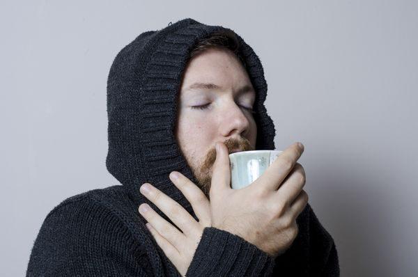 喉の痛みを飲み物で和らげる男性