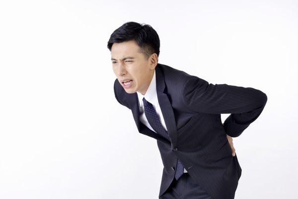 激しい腰の痛みにうずくまる男性