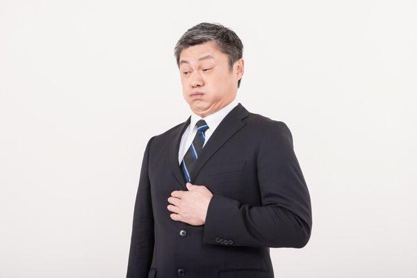 食べすぎで胃もたれしている男性