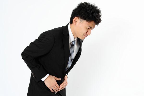 激しい腹痛でうずくまる男性