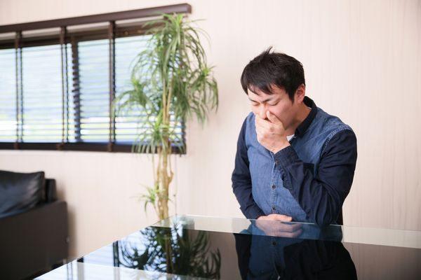 腹痛と吐き気に苦しむ男性