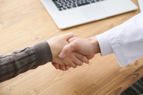 医師と握手を交わす患者