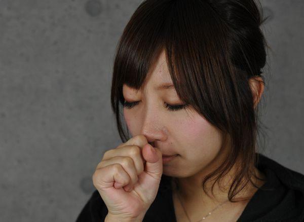 喉の痛みで咳をする女性